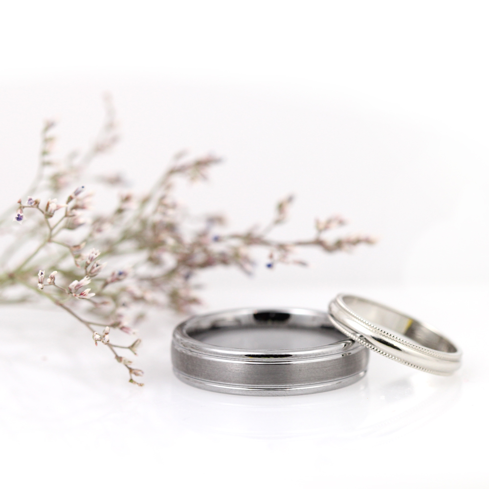 Durable tungsten wedding band with a satin finish center stripe and a dainty white gold band with a fancy milgrain edge.