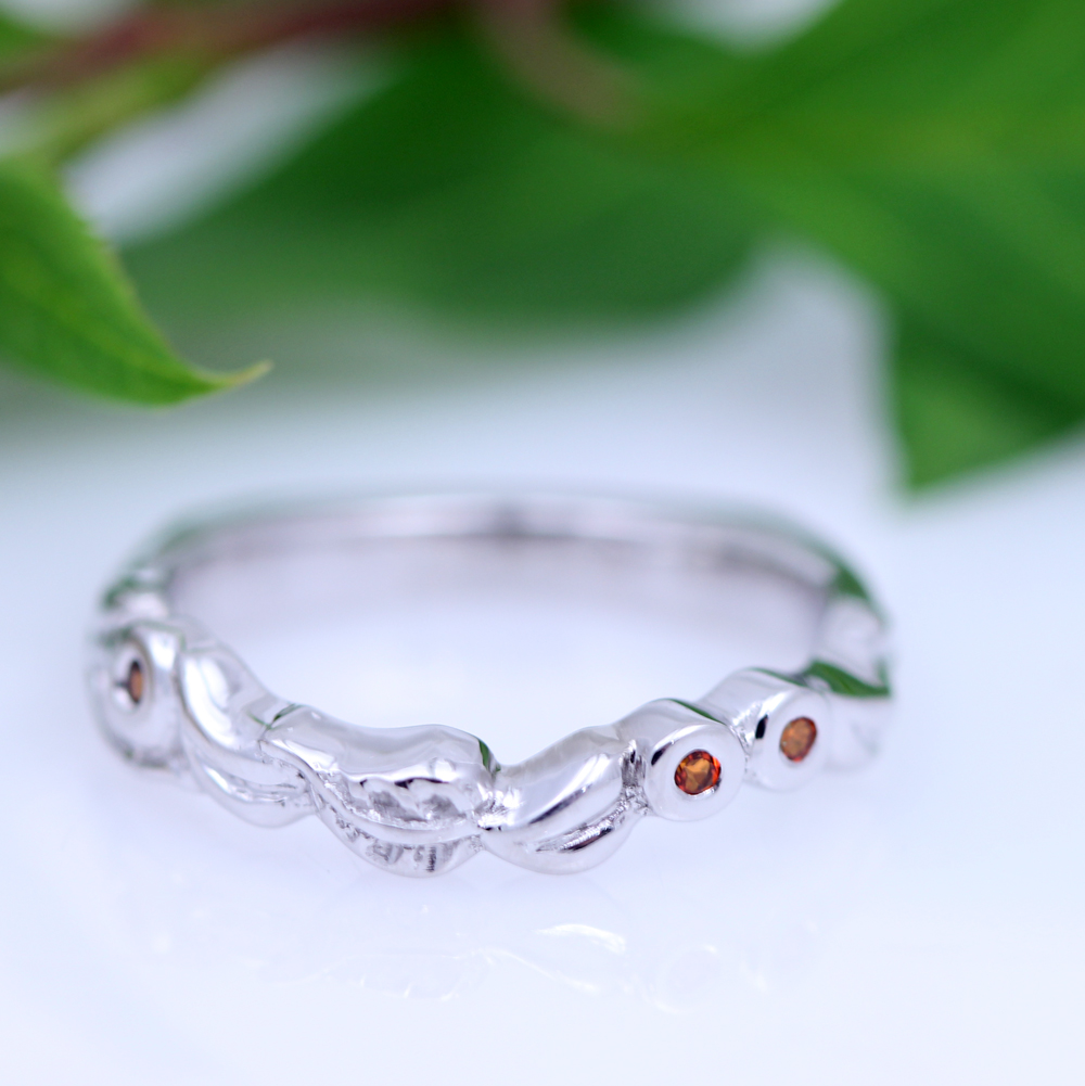 This garden inspired engagement ring features vibrant orange topaz amongst carved leaves for a lively, lovely contour wedding band.