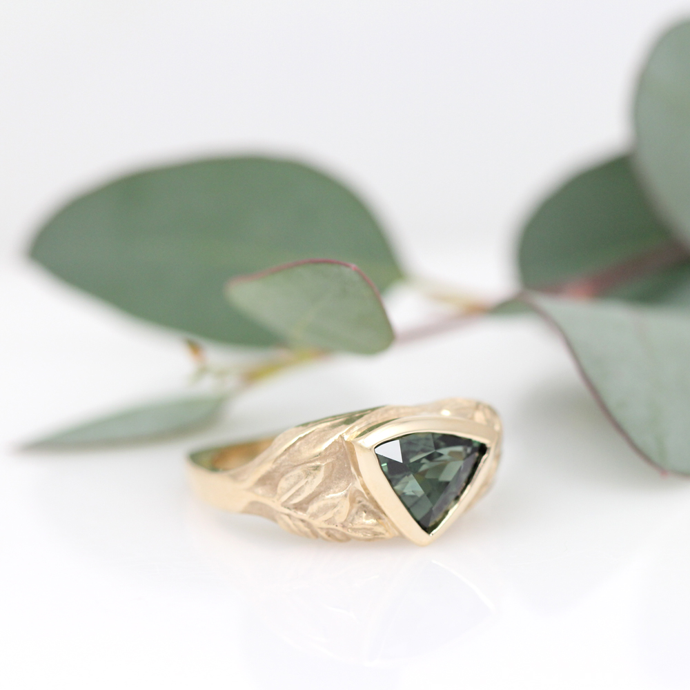 A trillion cut green sapphire shines in this leafy golden ring.
