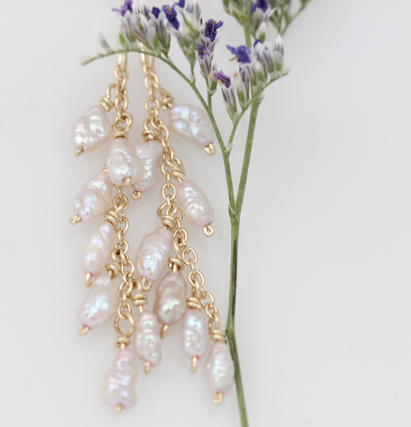 Pearl earrings featuring natural pearls wrapped by hand in yellow gold.