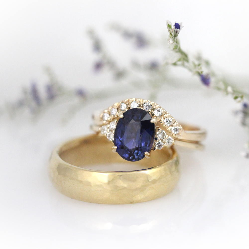 Wedding band set in yellow gold starring oval sapphire accented with moissanite.