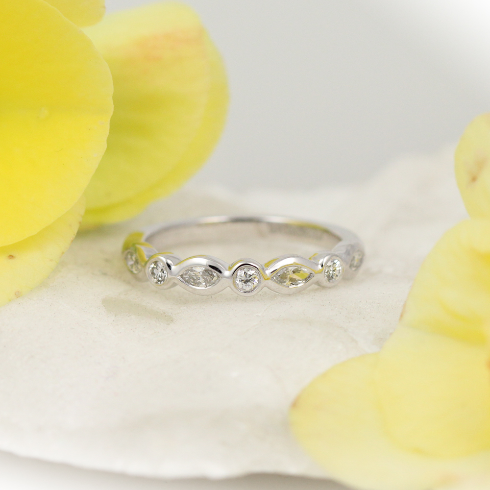 Marquis cut diamonds and round cut diamonds ebb and flow in this down to earth wedding band.