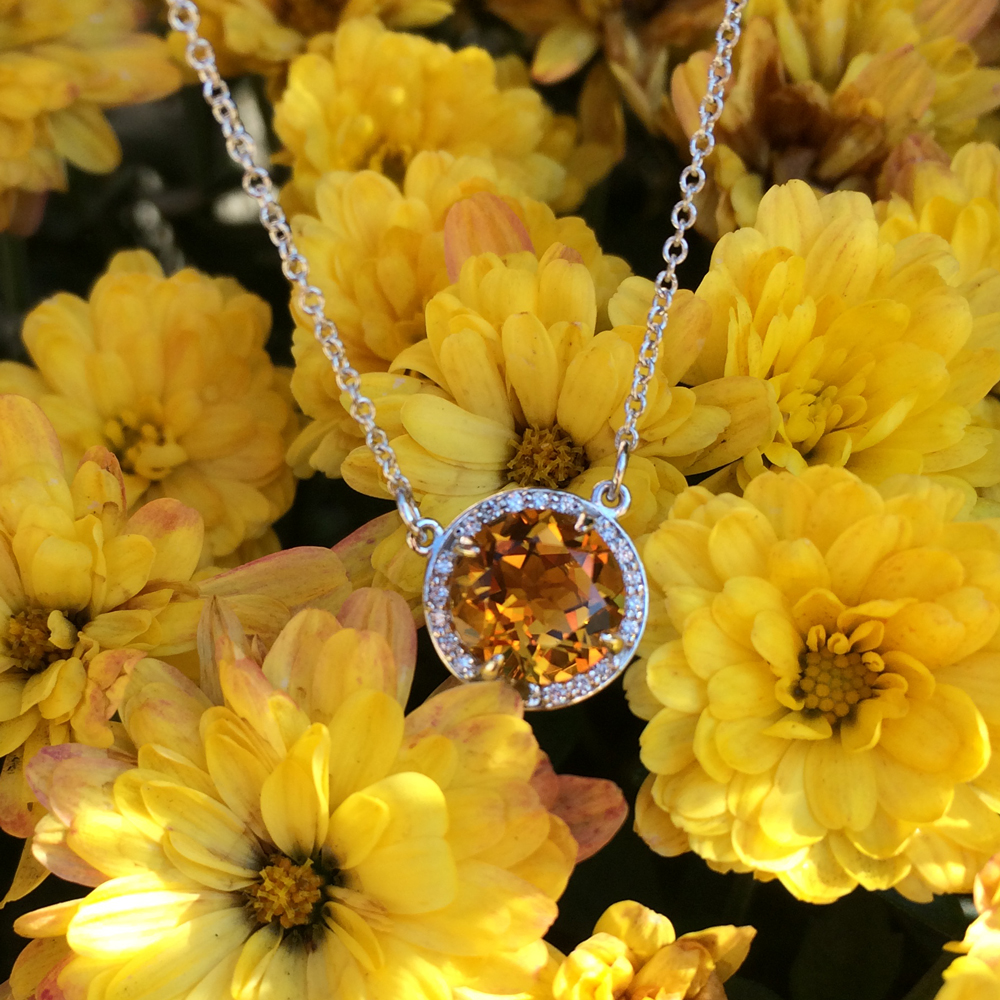 A sunny citrine glitters amidst a halo of white diamonds in white gold.
