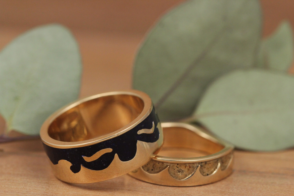 Gold wedding bands with sand inlays amongst beach waves.