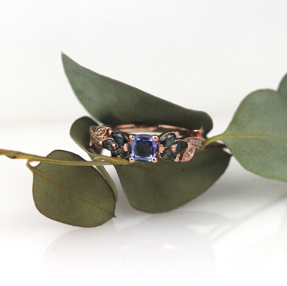 Hand picked white diamonds and sapphires in varying hues of blue and greens emphasize a stunning periwinkle cushion cut sapphire in this gorgeous rose gold engagement ring.