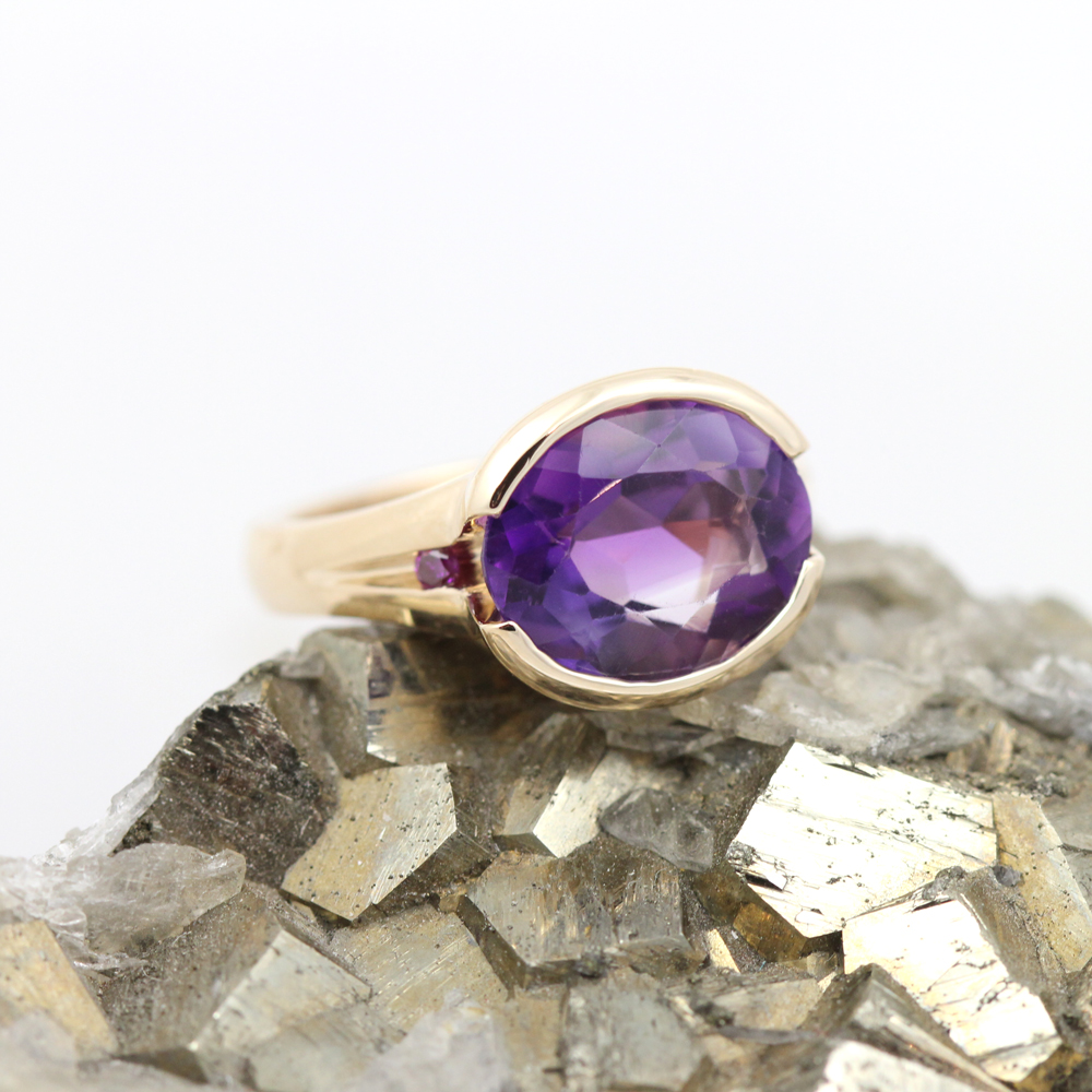 Bespoke three stone purple ring starring fine amethyst with royal purple diamond accents.