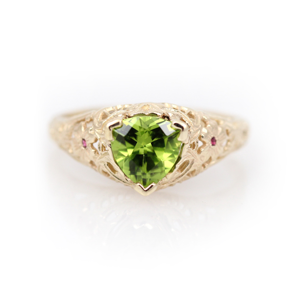Elegant scrolls and floral filigree heighten the drama of this stunning peridot and pink tourmaline antique reproduction ring.