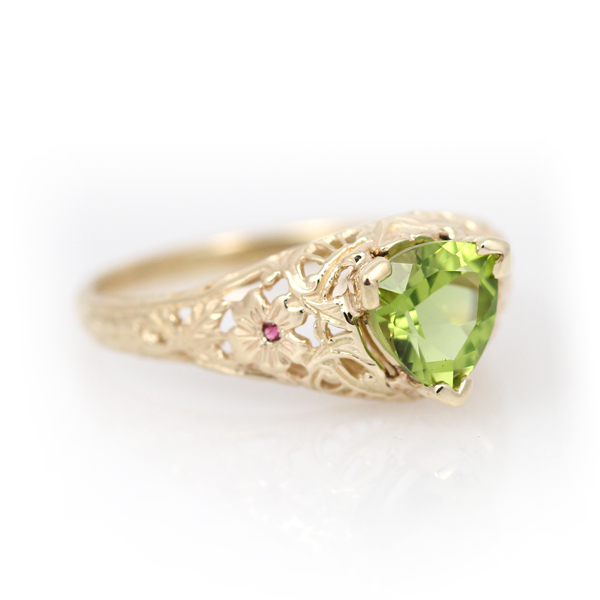 Antique reproduction ring with floral filigree, featuring a trillion cut peridot and pink tourmaline accents.