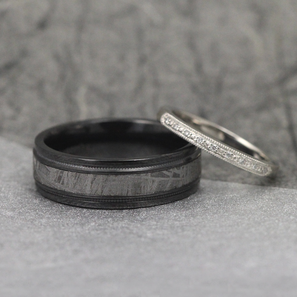 A modern black zirconium band with milgrain-edge meteorite inlay and a custom platinum diamond wedding band.