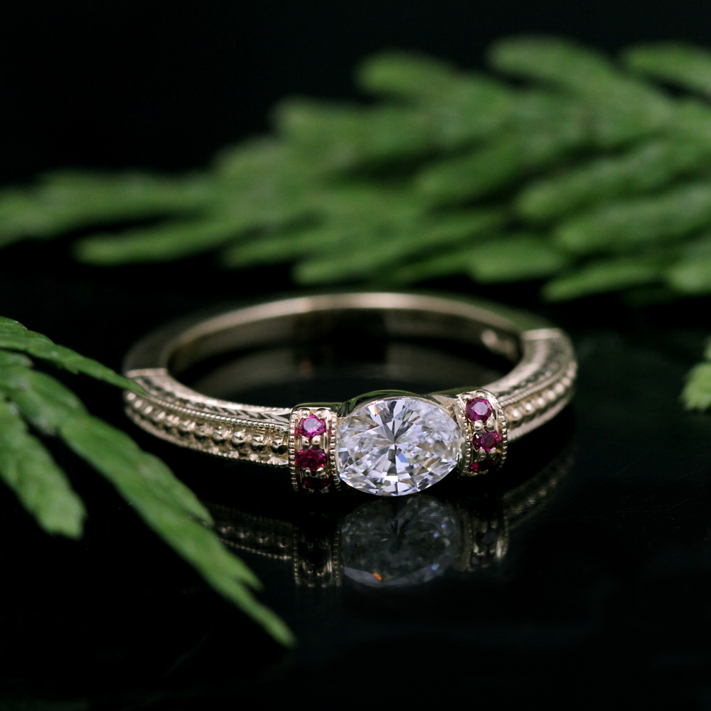 Vintage inspired engagement ring with antique style beading and milgraining highlighting an oval diamond with ruby accents.