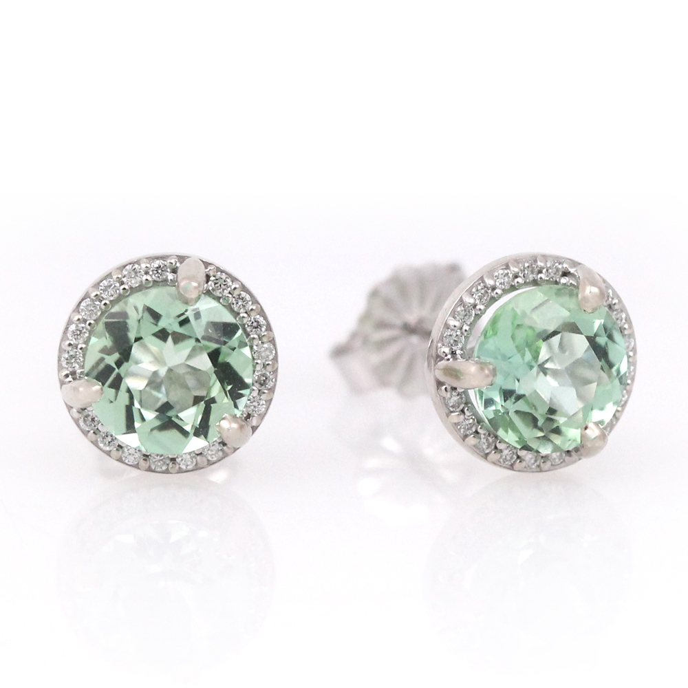 Soft hued green beryl surrounded by diamond halos.
