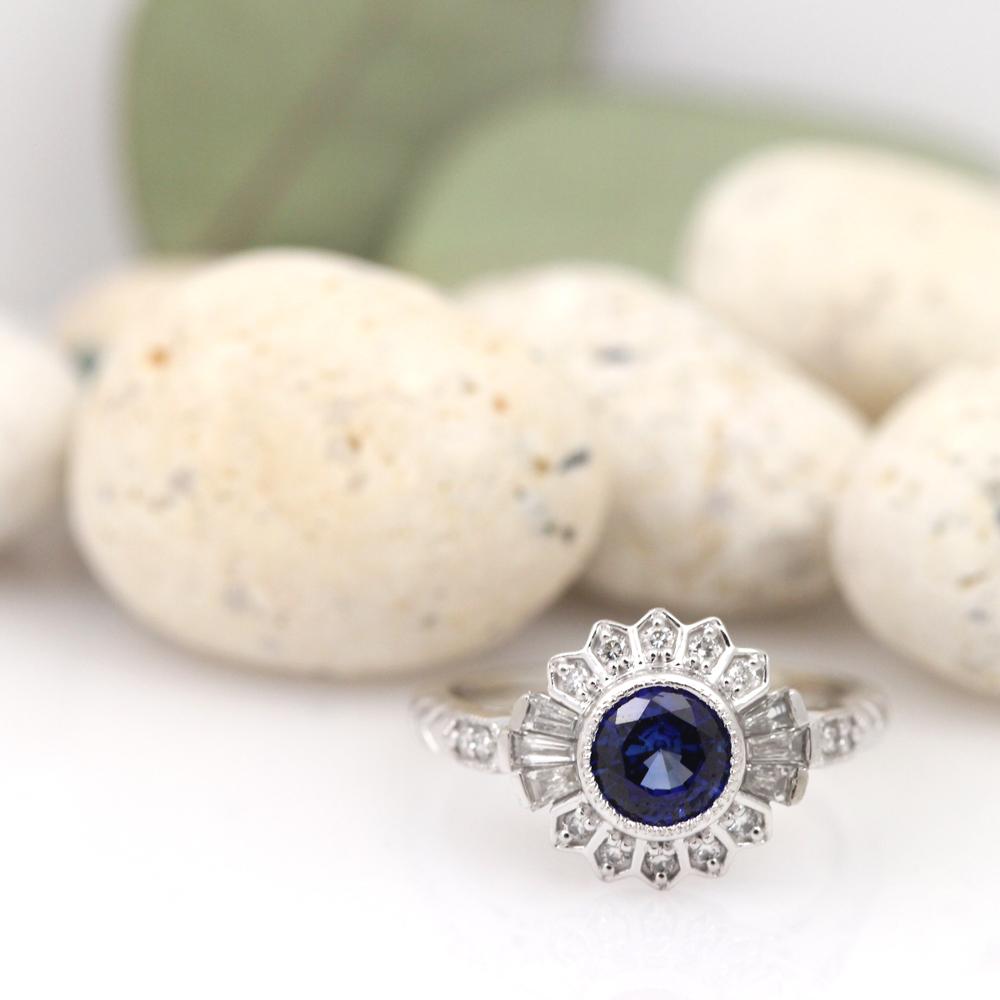 Art Deco inspired white gold engagement ring with blue sapphire and diamond accents.