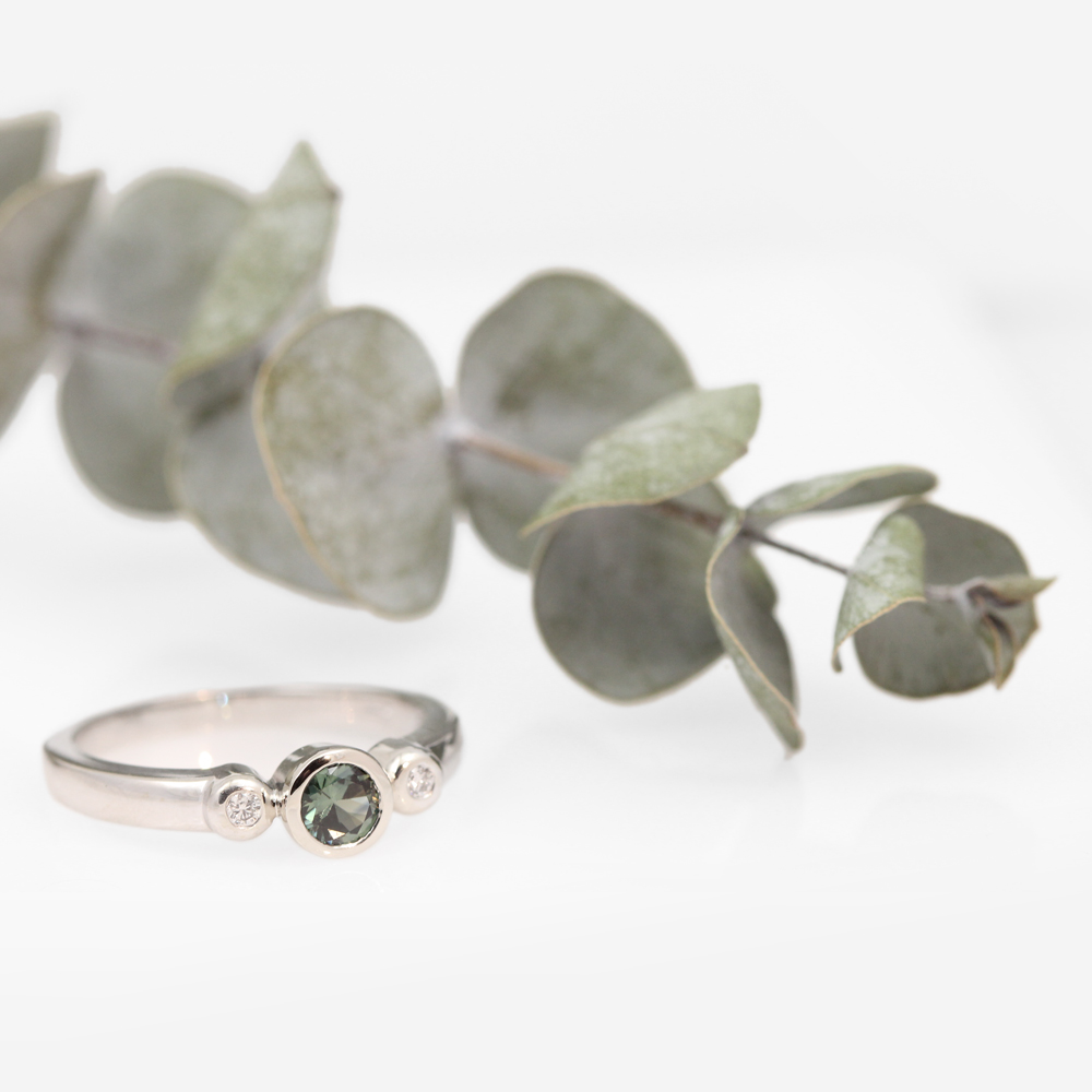 Green sapphire three stone engagement ring with diamonds in white gold.