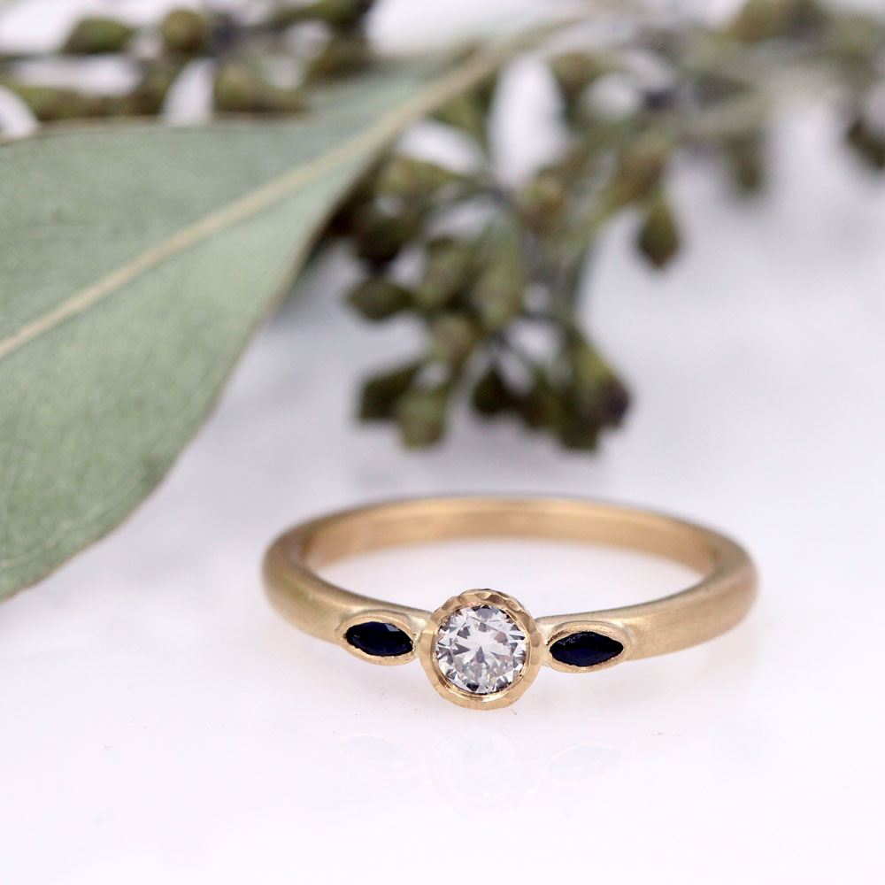Delicate matte engagement ring with three stone design in 18ky featuring heirloom diamond and marquise blue sapphires.