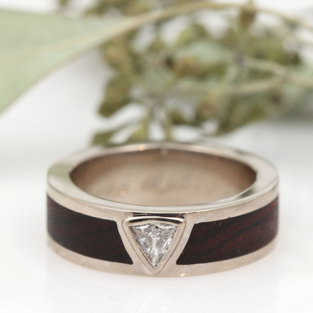 A bespoke Ironwood inlay in 18k white gold with a handpicked trillion cut diamond center.