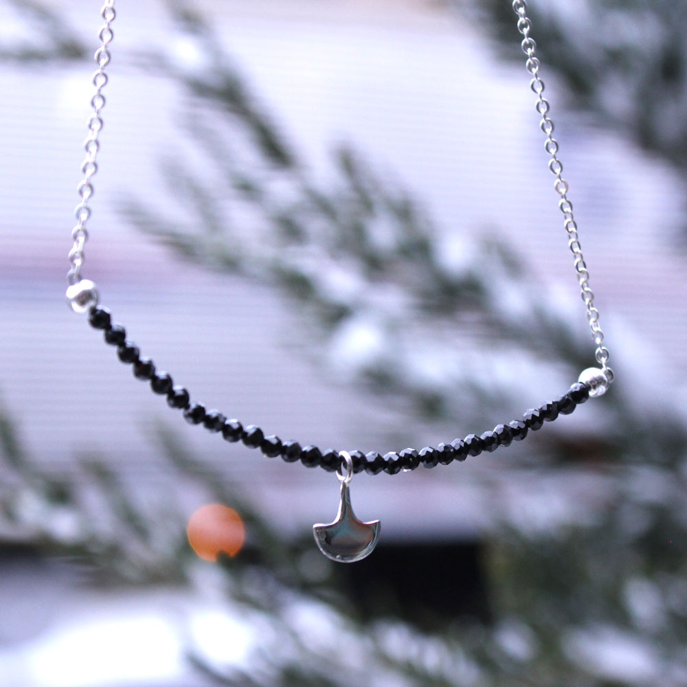 Black spinel beads featuring a tiny axe for those times when you're tough and pretty.