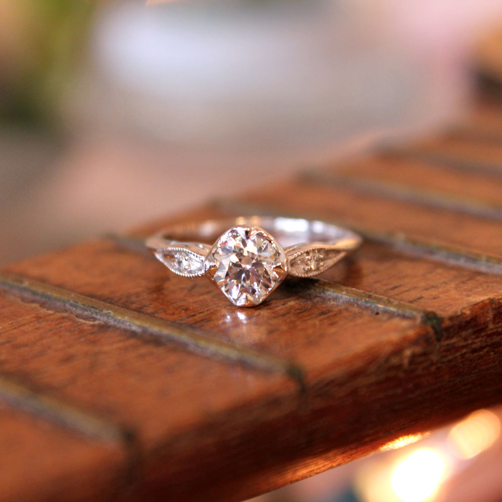 Diamond engagement ring with vintage inspired details in white gold.