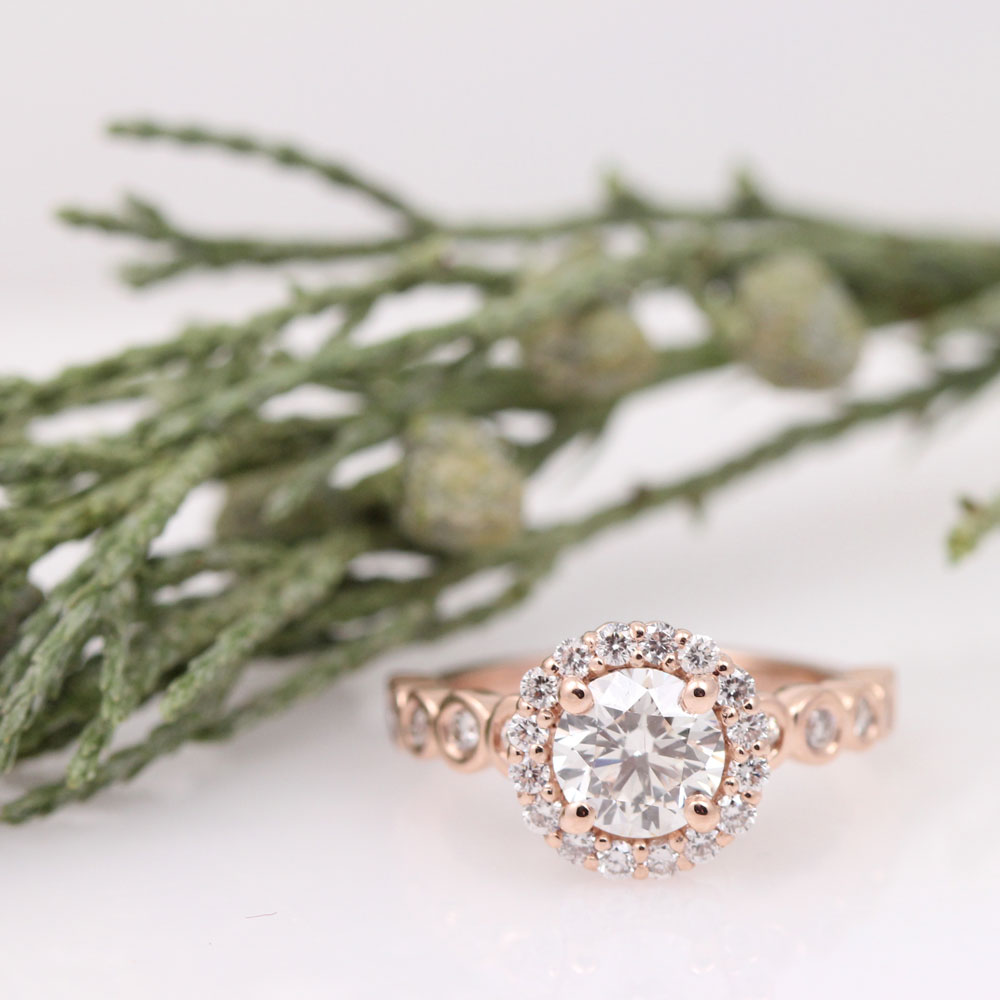 Bespoke rose gold diamond halo engagement ring with bubble bezel set diamonds down the shank.