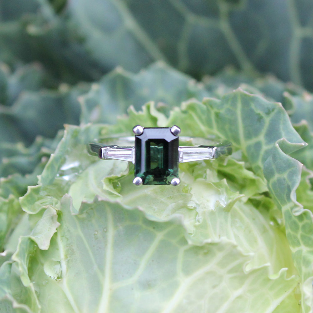 Timeless emerald cut diamond three stone engagement ring, starring a vivid green diamond and bright white diamonds in platinum.