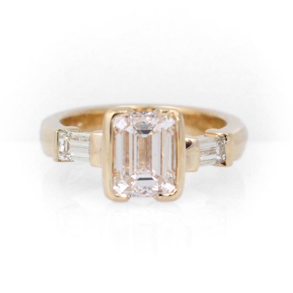 Bespoke emerald cut diamond three stone engagement ring.