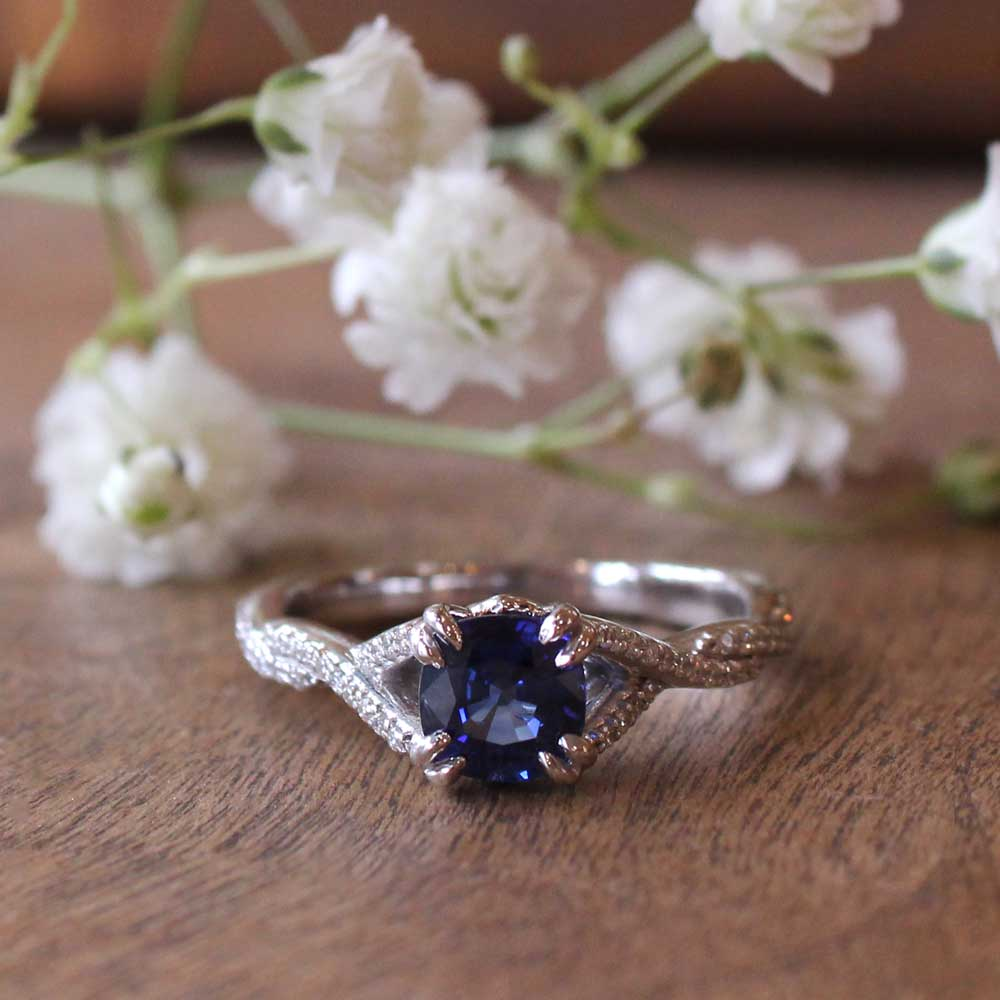 Sapphire engagement ring with twisting pave diamond band.